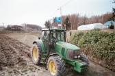 子どもと父がトラクターで畑を耕している